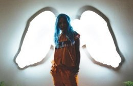 Halsey standing in front of neon wings promoting her album Hopeless Fountain Kingdom