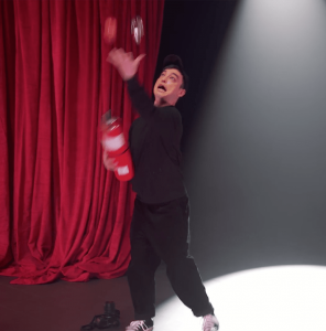Screen capture from Joji's Extravaganza - Joji is juggling fire extinguishers and iPhones