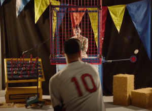Screen capture from Joji's Extravaganza - Joji is sitting above a dunk tank while a baseball pitcher throws a perfect shot at the lever